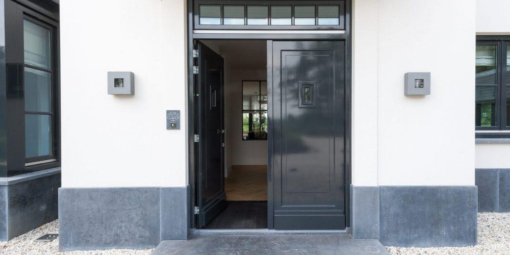 Stalen binnendeuren en binnenraamIn een woning met bijgebouwen heeft DittmarDesigns een aantal stalen deuren en een binnenraam ontworpen. Bij binnenkomst door de voordeur geeft het royale raam meteen een weids uitzicht. Je vangt een glimp op van de woonkamer en kijkt dan via de serre zelfs ver de tuin in.